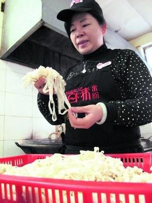 图为自强不息的下岗女工谢典均在加工自己的米粉。刘炬 摄