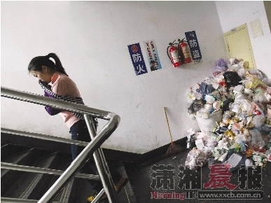 昨日,湖南财政经济学院望舒学苑3栋女生宿舍,一女生捂着鼻子经过堆满垃圾的楼梯间。 图/记者刘有志