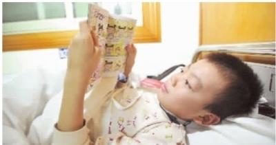 11月3日上午,长沙市中心医院胸科病房,军军躺在病床上看护士阿姨送给他的漫画书。 记者 田超 摄