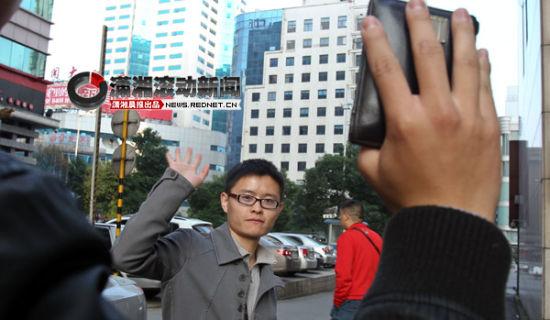 (11月10日下午,彭亚将捡到的钱包还给王先生后挥手告别。之前他通过微博找寻失主。图/潇湘晨报滚动新闻记者 殷建军)