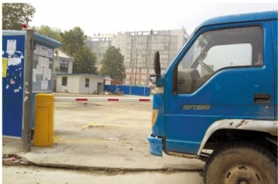 长沙市天心区新开铺,其中一处关闭的停车场,工人正在里面修整场地,而货车都只能停在外面的马路上。 记者 李琪 摄