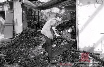 昨日,长沙市天心区西湖路282号,火灾现场已经拉起警戒线,店内是一片狼藉,一位中年男子正在清理现场。图/记者徐夏霏