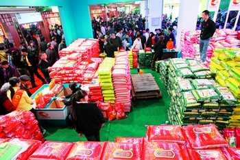 """(昨日是第十届湖南(国际)农博会最后一天,参展商纷纷将产品打折甩卖,市民也抓住这难得的机会,大包大包买""""年货""""。图为米摊前排起了买米的长龙。贺文兵摄)"""