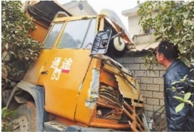 11月17日,长沙市雨花区扬子路上,一辆重型渣土车冲进路边一户民居的车库中,车辆房屋损毁严重。记者 童迪 摄