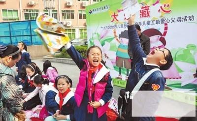 11月19日,在省儿童医院大门前,长沙市枫树山小学100余名小学生为千里来长沙做心脏手术的藏族女孩小卓玛爱心义卖。