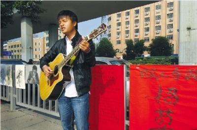 """昨日,汽车西站附近,23岁的周攀拿把吉他深情歌唱。他身后,还贴着一张""""天下英雄帖"""":招募有才艺的农民工。图/记者辜鹏博"""