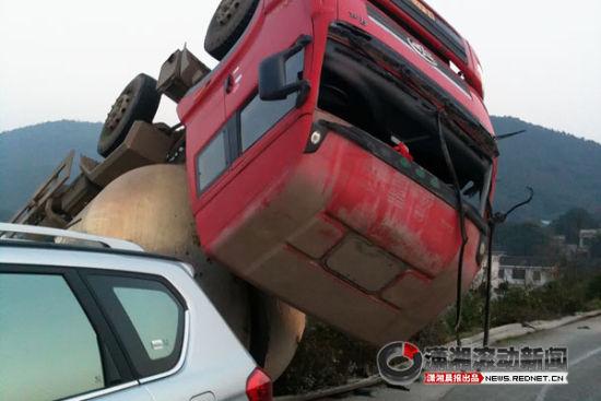 (水泥罐车在行驶时失控,四脚朝天摔在高速公路的护坡上。图/潇湘晨报滚动新闻记者 陈斌)