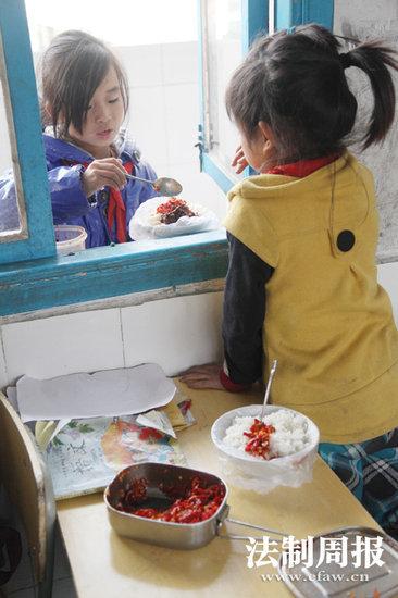 四年级的龙张欢(窗外)与三年级的王艳是一个村的,两人常在一起吃饭。