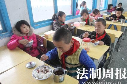 """四年级的学生在吃早饭,在山江镇完小学生们一日三餐都是吃白米饭加自带的""""罐头菜""""。"""