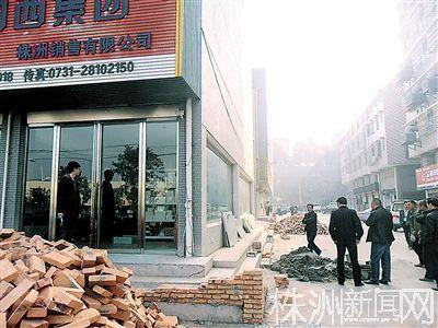 昨日,王建平的店铺周围砌了一堵约20厘米高的红墙。周宇欢/摄
