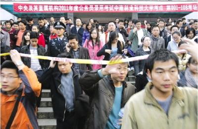 2010年12月5日,2011年度公务员考试中南林业科技大学考点,考生们穿过警戒线走出考场。资料图/记者韩敬宇