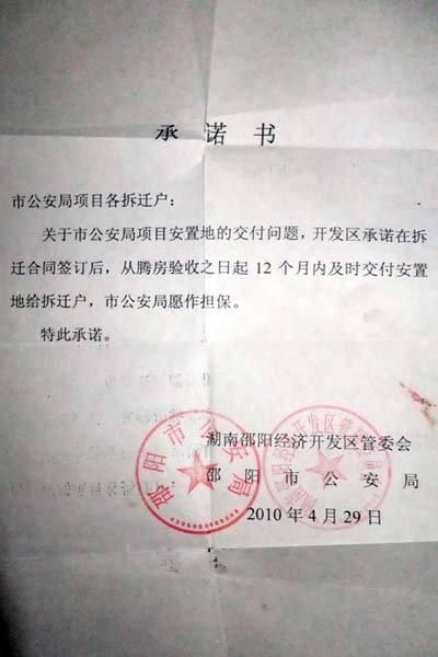 """邵阳市公安局的承诺书承诺书中写到:""""从腾房验收之日起12个月内及时交付安置地给拆迁户""""(记者 白宇 马文佳 摄)"""