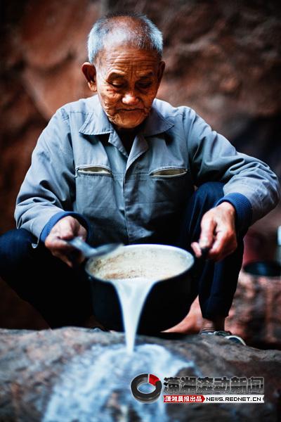 (李高帮正在淘米准备做饭。图/潇湘晨报滚动新闻记者 杨抒怀)