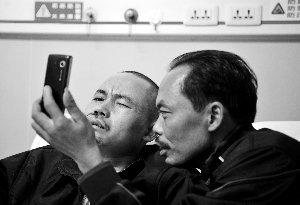 谢桐军(左)的家人播放用手机录制的目击人的视频,但谢桐军却很难回想起当时的经过。新华社发