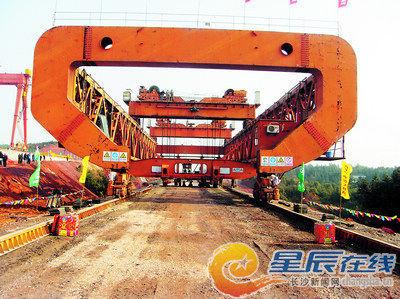 昨日上午,架桥机将长32.6米、宽12米、重800余吨的预应力混凝土箱梁平稳、精确地架设至长昆湖南段寺头冲大桥。陈晨 小刘军 摄影报道