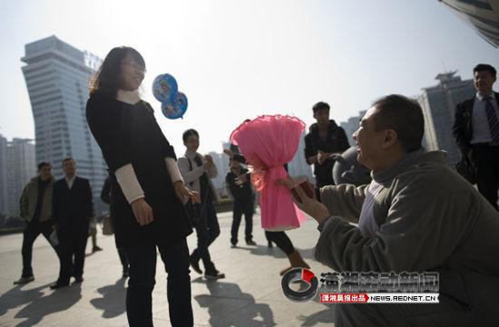"""(邓先生装扮成""""灰太狼"""",在广场上向女友求婚,引来众人围观。图/潇湘晨报滚动新闻记者 张轶)"""