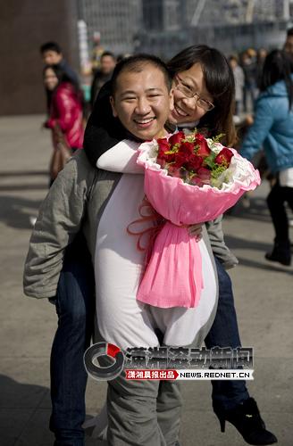 """(扮成""""灰太狼""""的邓先生背着女友,开心地走向幸福之路。图/潇湘晨报滚动新闻记者 张轶)"""