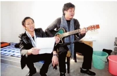 12月12日,长沙市朝阳街道向韶社区,吉他手王成勇(右)和伙伴卓善达在宿舍内练习原创歌曲。记者 范远志 摄