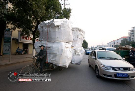 (长沙市杨家山环线,一男子骑着一辆满载泡沫的三轮车在车流中穿行。图/潇湘晨报摄友团 卢七星)