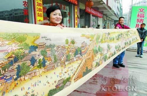 郭泽兰与她绣制的《清明上河图》。(记者 张哲 摄)