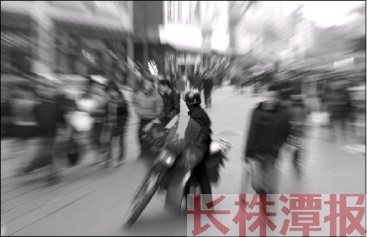 12月25日,株洲市芦淞市场群,人来人往的街道上,一辆摩托车停在路中间。虽然摩托飞车贼一般在偏僻地出现,但听见背后有摩托车声音时,一样需要提高警惕。本报记者 陈正 摄