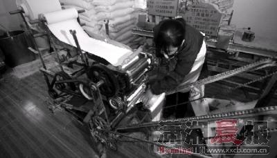 12月26日,米粉制造点内一名工人没有戴口罩和手套,直接用手拿起快掉落在地上的面条。组图/记者辜鹏博