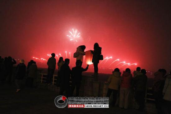 2011年12月31日,长沙湘江边,一些市民在这里看烟火放孔明灯。图/潇湘晨报滚动新闻记者 记者华剑