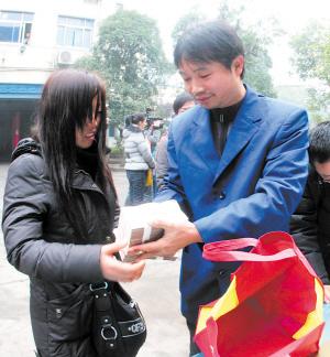 昨日10时30分,在蓝灯的士公司,失主从的哥刘小聪(右)手中接过失而复得的15万现金。余志雄 摄