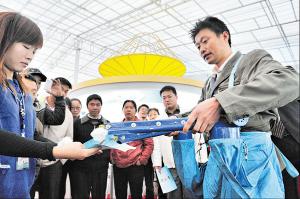 2011年科交会上,周红灯现场操作他发明的棉花采摘器。通过这个来自生活中的发明,他轻松地把棉花一采而空。陈飞 摄