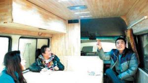 """胡晓聪介绍自己的""""房车"""",他说记者面前的这张桌子放下去就成了一张床。  网友""""关刀"""" 摄"""