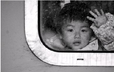 昨日,来自贵州的2岁男孩张俊杰在从杭州发往贵阳的列车上挥手告别。图/新华社