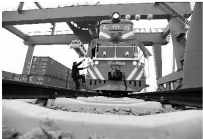 1月8日上午,长沙铁路新北站,工作人员爬上一辆装满集装箱的货车,准备开车出发。当日,该站正式开通营运。 记者 田超 摄