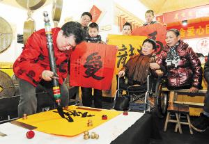 """在团圆宴上,中国铁笔书法家杨跃进捏着铁笔,书写了""""爱""""、""""善""""、""""龙""""等作品分别送给许月华和彭水林。  石祯专 周和平摄影报道"""