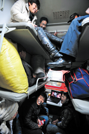 1月14日,在一列临客上,乘客挤在临时改为硬座的卧铺车厢内。杨晓原 摄