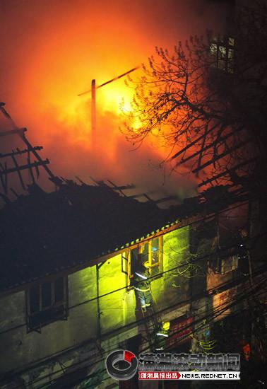 1月15日晚,长沙通泰街一栋两层老式住宅楼起火,消防人员通过梯子爬到2楼,朝里喷水灭火。图/潇湘晨报滚动新闻记者 刘有志