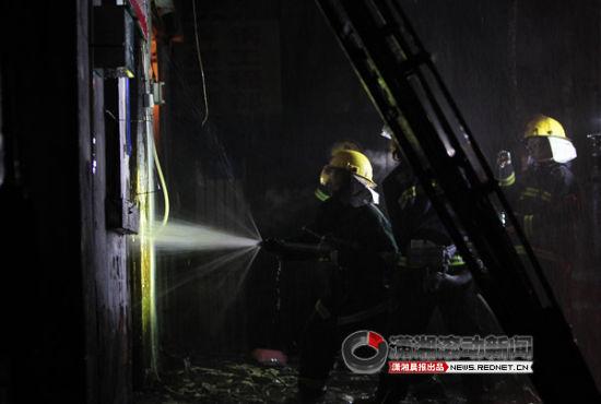 消防人员朝里喷水灭火。
