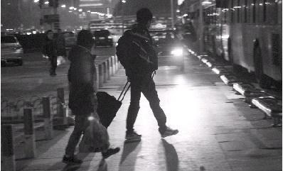1月26日,长沙火车站,灯光前,拖着行李箱匆匆行走在路上的市民。图/记者辜鹏博