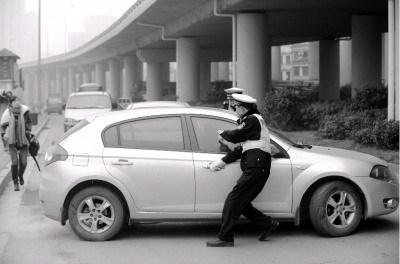 昨日下午,一辆中华小轿车看到交警,欲掉头逃跑。交警见状跑上前将其拦下。检查发现,这名驾驶员的驾驶证过期了,看到交警心虚想跑。图/记者邵骁歆