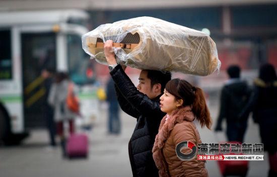(1月28日,长沙火车站,一位返程的旅客头顶行李箱走出车站。图/潇湘晨报滚动新闻记者 辜鹏博)