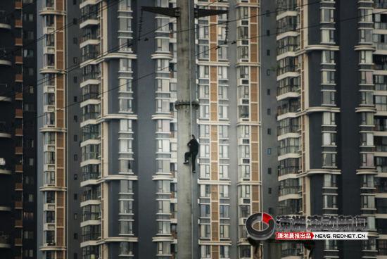 当代热点类单幅优秀奖:11月22日,四川成都,一名男子爬到电线杆上向当地政府要求房屋拆迁补助。图/徐少锋