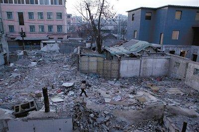 """昨日,一名小女孩从废墟上走过。位于东城区北总布胡同24号院的""""梁林故居""""已被拆除。本报记者 孙纯霞 摄"""