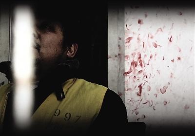 2月16日,在市第二看守所,许月在逮捕证上按下了自己的手印。身后墙上的红斑,也是一个个悔恨的印迹。周维欣/摄