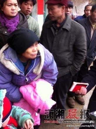 吴成枝老奶奶在救灾物资发放中心旁排队退钱。