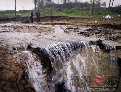 """2月22日,益阳市岳家桥镇岳家桥村,一条河流被""""天坑""""截断,河水灌入大坑形成小型的瀑布。 图/实习生杨旭"""