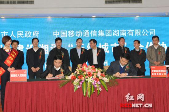 """(湘潭市委副书记、市长胡伟林(前左)与中国移动湖南公司董事长王建根签署协议,启动湘潭""""无线城市""""建设。)"""