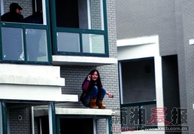 女孩蹲在32楼的飘窗外沿打着电话,左手腕被自己拿着石头划伤。