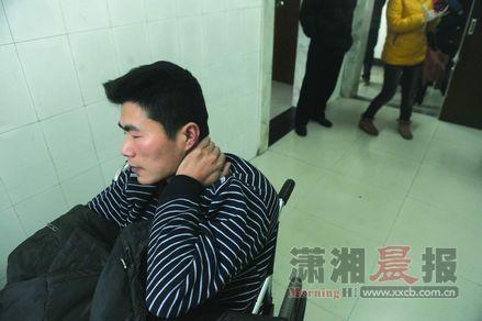 伤者杨俊坐在轮椅上等待检查,初步诊断他伤了腰椎。