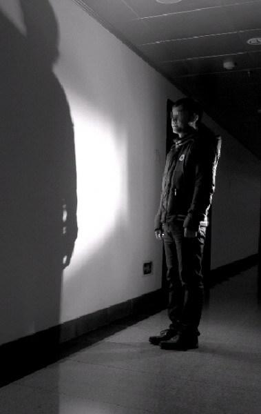 昨日,李明(化名)的身影被灯光打在墙面上,他说自己被别人冒名顶替报考了。图/记者沈荣华