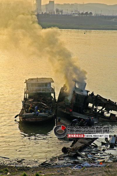 3月25日下午6时许,长沙市民朱先生路过湘江东岸猴子石大桥以南约1公里处,发现一只破旧的钢船倾斜于江面,还有烟冒出。图/朱先生 提供