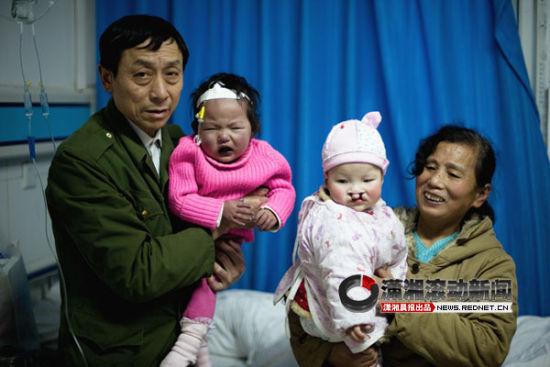 环卫工人刘启宣和妻子王解良抱着两名缺陷弃婴。图/潇湘晨报滚动新闻记者 张轶